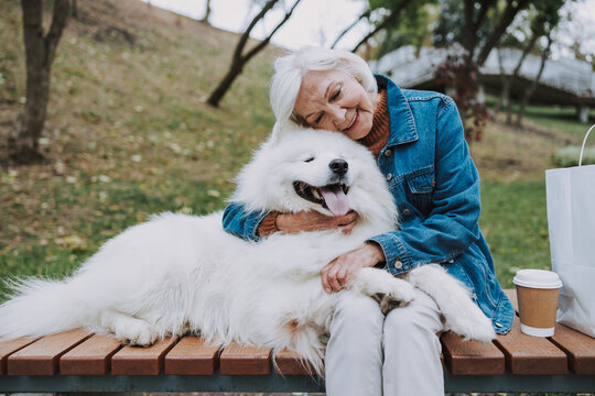 Caucasian smiling woman sitting on bench with dog