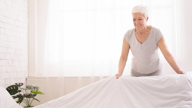 Senior woman making bed and organizing room in morning