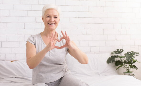 Cute senior woman making heart shape with her hands and fingers
