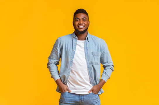 Portrait of handsome black guy standing with hands in pockets