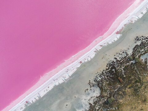 Aerial high angle drone view of Loch Iel, also called Pink Lake, near the village of Dimboola in Victoria, Australia. The pink color results from red pigment secreted by microalgae in summer.