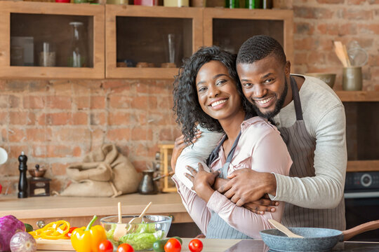 Handsome african man hugging his wife while cooking at kitchen