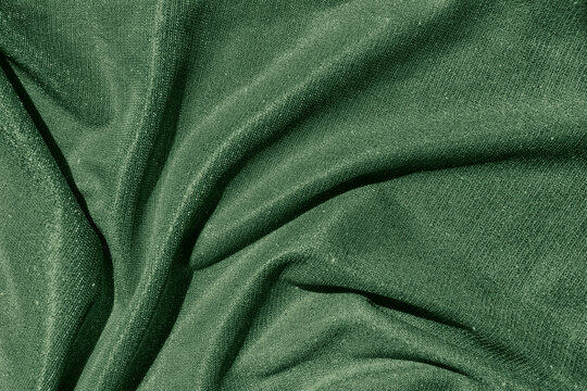 Dark green colored Background of draped fabric with silver lurex thread. Beautiful fashionable fabric with a shiny thread for making clothes. Textile texture. Color trend concept.