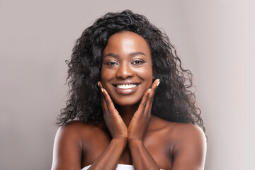 Fototapete - Beautiful african american woman touching her smooth skin on cheeks