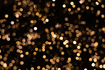 Blurry golden and white fairy string lights in dark night creating beautiful bokeh effect with glowing circles or shiny dots, abstract image for Christmas or holiday card, banner or background