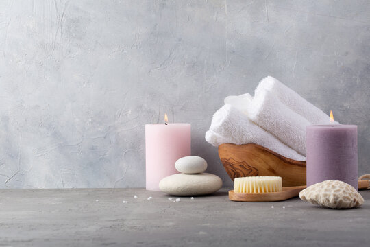 Spa and relax. Candles, stones and brush for body on grey background.
