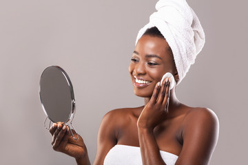Fototapete - Woman looking in mirror and cleaning face with cotton pad
