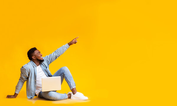 African man sitting with laptop and pointing at copy space