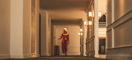 Full-length portrait of gorgeous lady with blonde hair wearing red jumpsuit walking along the hall in hotel with a suitcase. Business trip concept. Horizontal shot. Front view