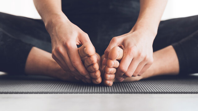 Woman sitting in lotus position with bare feet
