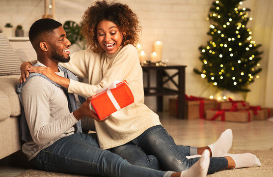 Handsome man surprising girl with Christmas present