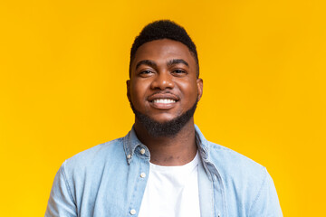 Portrait of confident black millennial guy over yellow background