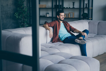 Photo of handsome guy watching happening in living room sitting comfortable couch relax saturday evening in modern flat loft indoors casual dressed Wall mural
