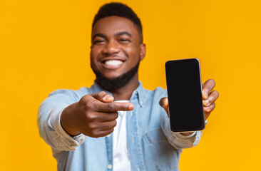 Cheerful african guy pointing at smartphone with black screen
