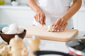 Cropped close up photo of stylish woman gourmet veggie cut mushroom on chopping board prepare fest have bowl with fresh eggs in house white kitchen Wall mural