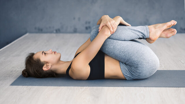 Woman practicing yoga, lying in knees to chest pose