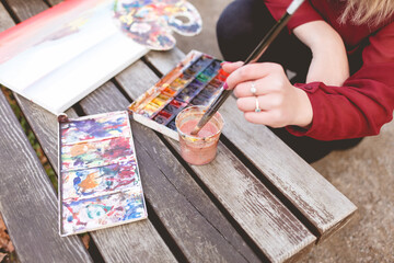 Woman draws a picture on a park bench. Blonde artist engaged in her favorite hobby of drawing.  Drawing accessories