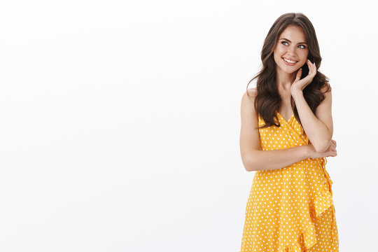 Gorgeous thoughtful intrigued young fashionable woman in yellow casual summer dress, touch cheek lovely smiling gazing upper left corner curious, thinking, check out promo, white background
