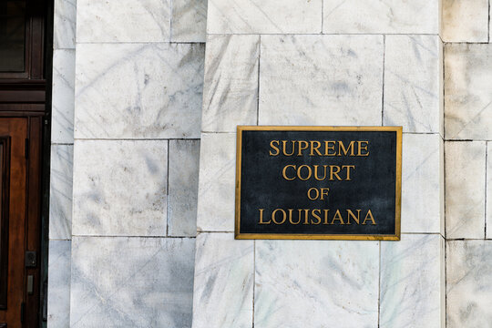 New Orleans, USA - April 23, 2018: Old town Royal street in Louisiana famous town city with exterior closeup of sign for entrance to Supreme Court building