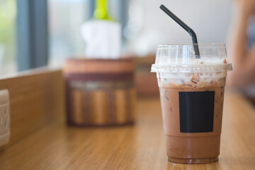 Iced coffee mocha in takeaway cup on wood table