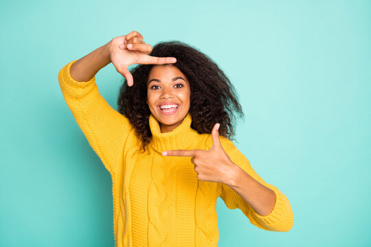 Photo of amazing dark skin lady making imaginary frame cadre of camera taking shot wear yellow knitted pullover isolated blue teal color background