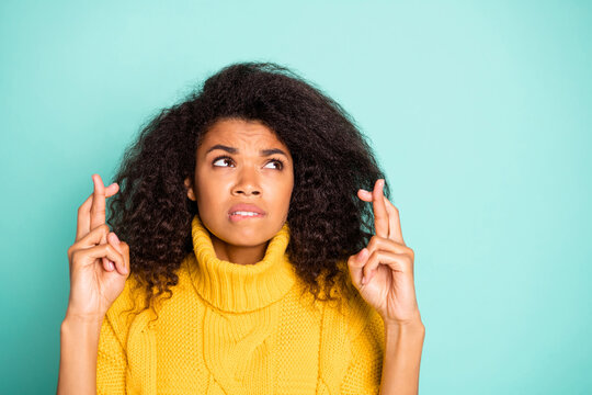 Closeup photo of amazing dark skin lady holding crossed fingers biting lips worried about school test wear yellow knitted jumper isolated blue teal color background