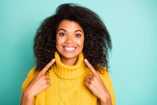 Closeup photo of amazing dark skin curly lady indicating fingers on perfect teeth advising dentist wear yellow knitted pullover isolated blue teal color background