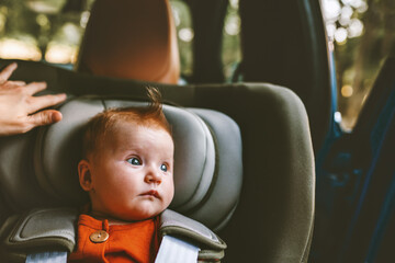 Baby sitting in safety rear-facing car seat looking at window family lifestyle vacations road trip child security transportation