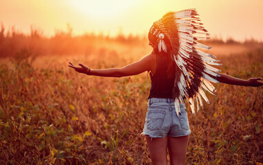 American Indian girl in wild nature at the sunset.