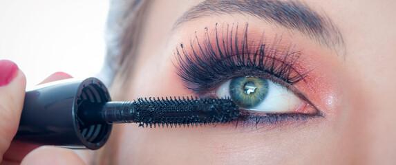 Makeup professional artist applying mascara on lashes of model eye