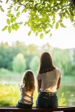 Rear view of young mother and small daughter sitting on the bench in park