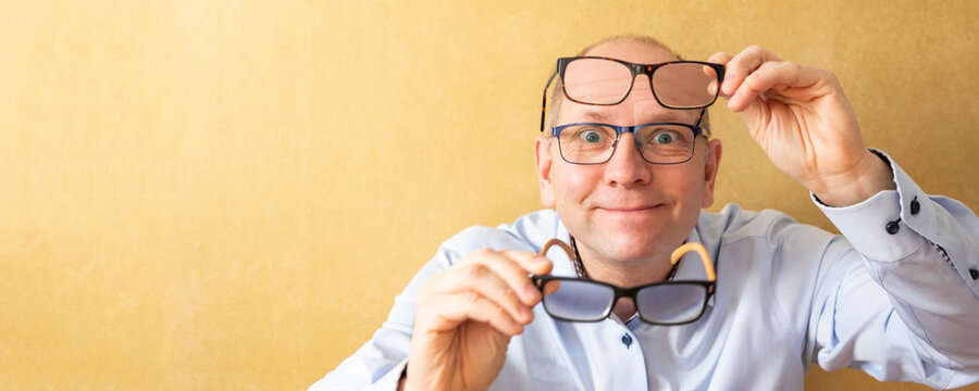 A man tries on reading glasses. He tests glasses and has three points on his face. Portrait of a European man in a blue shirt. Orange wall and copy space
