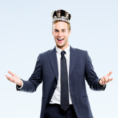 I am business king! Portrait of happy smiling young businessman in fake crown, isolated over grey color background. Leadership and business success concept picture