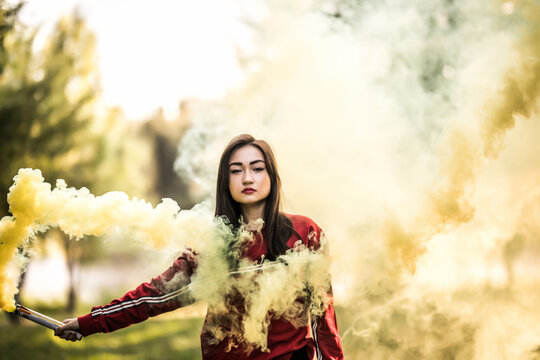 Young asian woman holding yellow colorful smoke bomb on the outdoor park. Yellow smoke spreading
