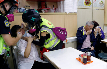 """People receive help from first aid volunteers after the police fired tear gas to disperse anti-government protesters, at a restaurant during a march billed as a global """"emergency call"""" for autonomy, in Hong Kong"""
