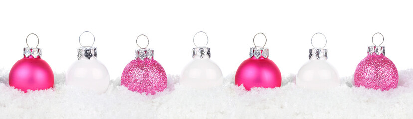 Christmas border of shiny pink and white baubles resting in snow isolated a white background