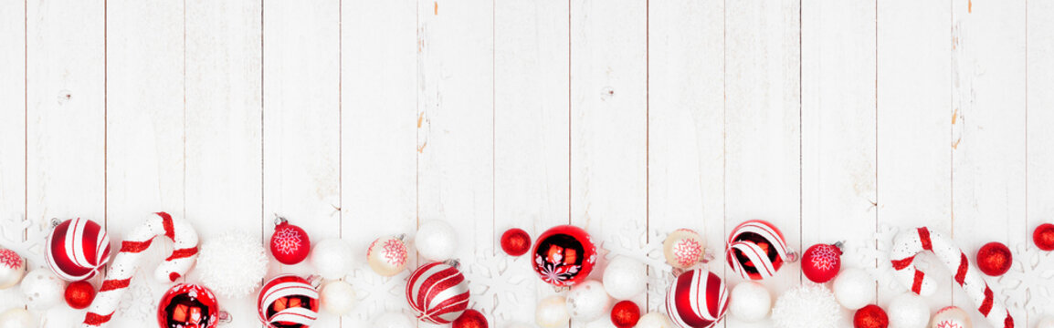 Christmas bottom border banner with red and white ornaments. Top view on a white wood background with copy space.