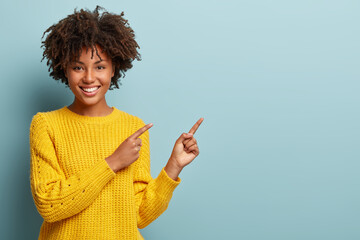Cheerful Afro woman points away on copy space, discusses amazing promo, gives way or direction, wears yellow warm sweater, has pleasant smile, feels optimistic, isolated over blue background