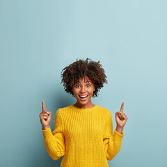 Gorgeous cheerful smiling woman with Afro hairstyle, points up, shows cool promo or amazing offer, recommends going upstairs, dressed in yellow sweater, gives advice, poses against blue background