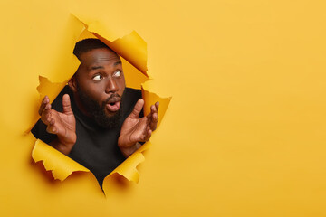 Shocked dark skinned man spreads palms sideways, reacts with surprisement, looks aside, wears black clothes, focused aside with impressed expression, poses in torn paper hole, yellow background