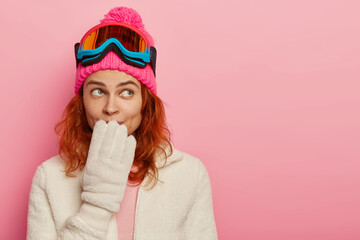 Poster Glisse hiver Portrait of snowboarder woman has thoughtful expression, keeps hand on mouth, wears winter hat, white gloves and ski mask, imagines nice trip to mountains, goes in for sport durimg cold weather