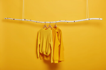 Selective focus. Three items of clothes on hangers. Long sleeved yellow jumpers on wooden rack near bright vivid wall. Copy space for text. Various casual outfits hanging in row at dressing room