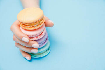 Beauty hand girl with trendy manicure taking color macarons on blue background