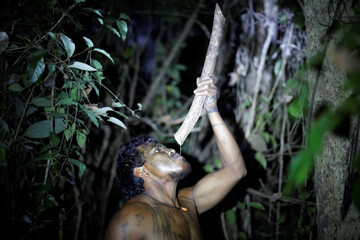 Indigenous leader Paulo Paulino Guajajara drinks water from a tree branch at a makeshift camp on Arariboia indigenous land near the city of Amarante