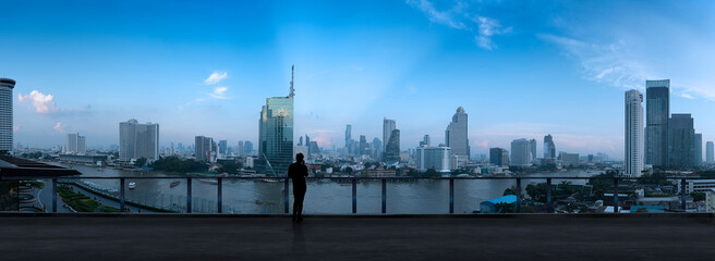 Fotomurales - Businessman standing using smart phone on open roof top balcony watching city night view.Business with ambition and vision concept.