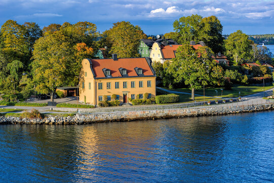 Yellow ancient house with red tiled roofs on waterfront of island Djurgarden at bright sunny day with autumn forest on the background. Stockholm, Sweden.