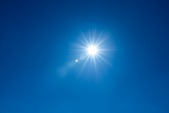 Sun, sunbeams against blue sky - cloudless heaven. Photography with Lense flair effect