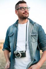 Hombre joven y sonriente con cámara de fotos analógica en medio de un desierto