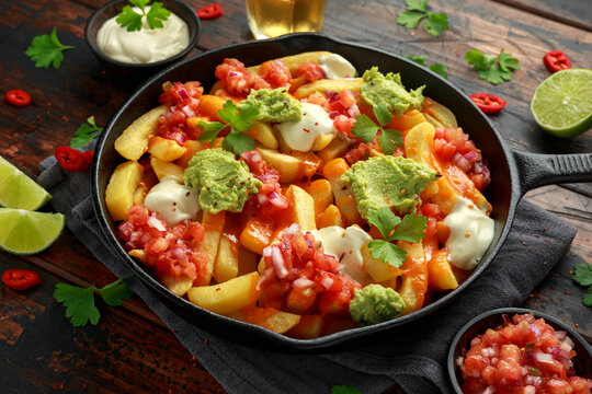 Loaded potato nachos with melted cheddar cheese, sour cream, tomato salsa, chilli, guacamole and beer