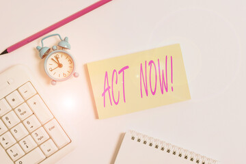 Text sign showing Act Now. Business photo text do not hesitate and start working or doing stuff right away White pc keyboard with empty note paper and pencil above white background